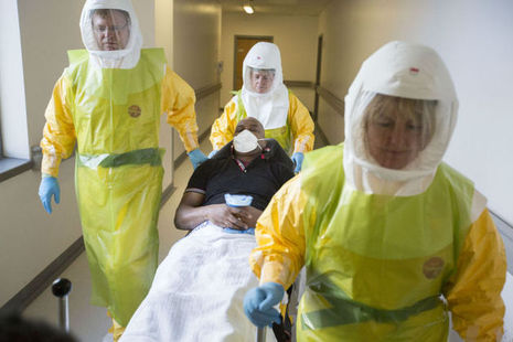 Medical personnel in protective clothing with patient