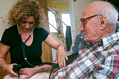 Carer taking pulse in the home