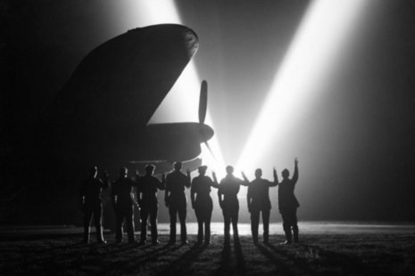 Ground crew on a RAF Bomber Command station in Britain return the V-sign to a neighbouring searchlight crew . Silhouetted is the nose of a Lancaster. [Picture: Imperial War Museum CH 15165]