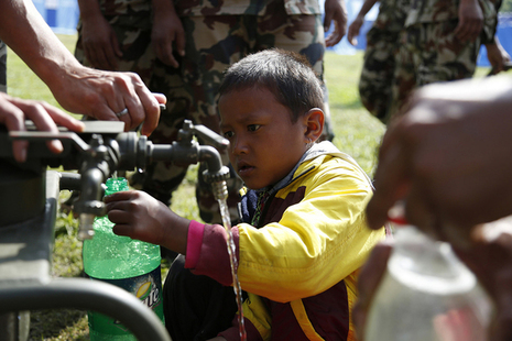 A Nepalese boy collects water from a pump installed by British Gurkhas after the earthquake which hit the country in April 2015. Picture: Jess Lea/DFID