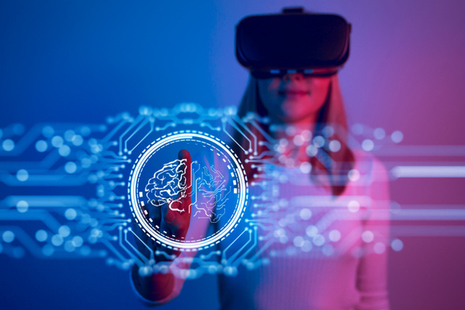 Woman in a VR headset pointing to a virtual touch screen (credit: Vertigo3d / iStock)