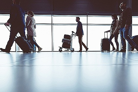 People walking with luggage through an airport terminal