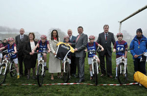 Children on bikes in field with minister Helen Grant