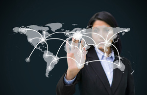 Businesswoman touching holographic image of the globe