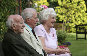 A group of 3 old age pensioners sitting happily on a bench