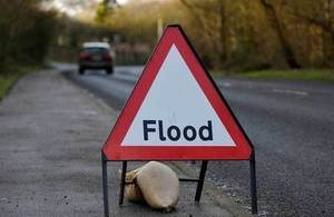 Flooding sign with sandbag