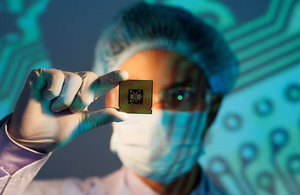 Person in lab holding semiconductor