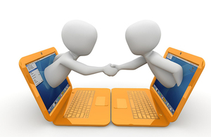 two animated people reaching out of laptops to shake hands