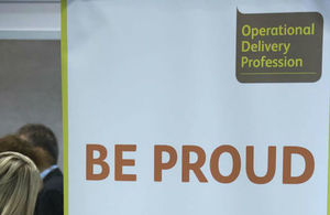 Photo of an Operational Delivery Profession wing banner saying 'Be Proud' with the Ops Del logo in the top corner