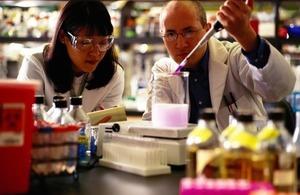 Male and female technicians performing a scientific experiment in lab