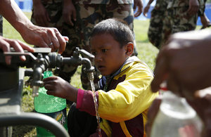 A Nepalese boy collects clean water from a pump installed by British Gurkhas after the earthquake which struck Nepal on 25 April 2015. Picture: Jess Lea/DFID