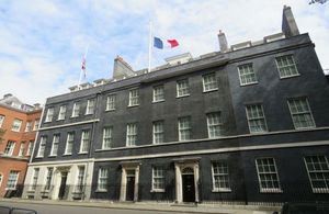 Picture of Downing Street 10 with the French and Union flag hanging at half mast