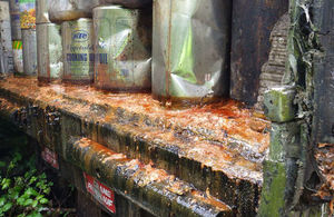 Tins of cooking oil leaking over rear lip of transport truck
