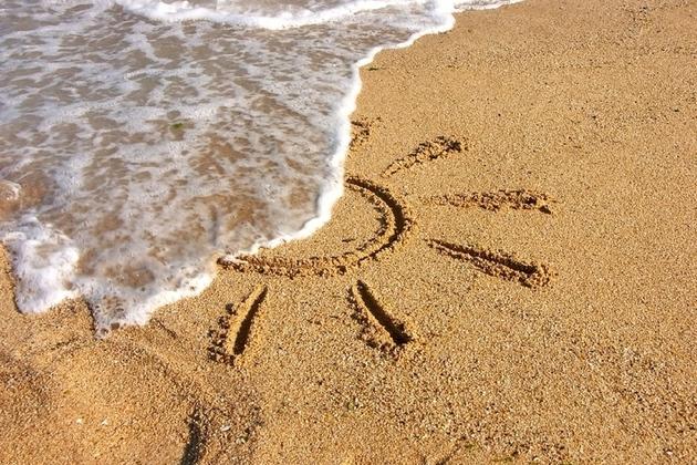 sun drawn in sand with sea washing it away
