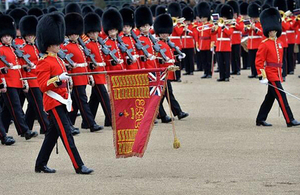Grenadier guards marching with a flag