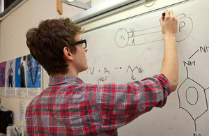 Teacher in front of a whiteboard that is showing chemical formulae