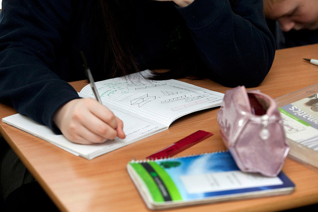 Student writing in a maths exercise book