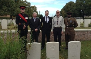 Guy Boxall (son of Gary Boxall), Gary Boxall great grandson of CSM Gale and representatives stand by CSM Gale's headstone - Crown Copyright - All rights reserved