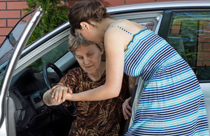 women helping an elderly lady from a car