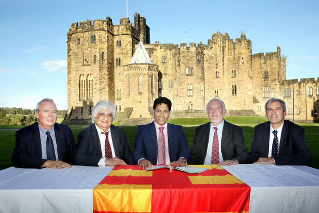 Leaders from Norhtumbria and India signing the agreement with Alnwick Castle in the background