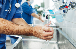 Doctors washing their hands to prepare for surgery.