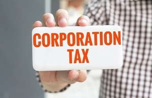 Hand holding card with the words corporation tax