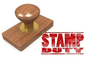 A wooden stamp with the words stamp duty written in red