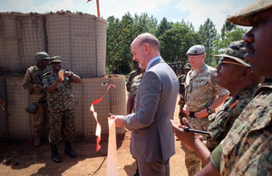 H.E. Peter West cuts tape as he hands over new Forward Operating Base to the UPDF
