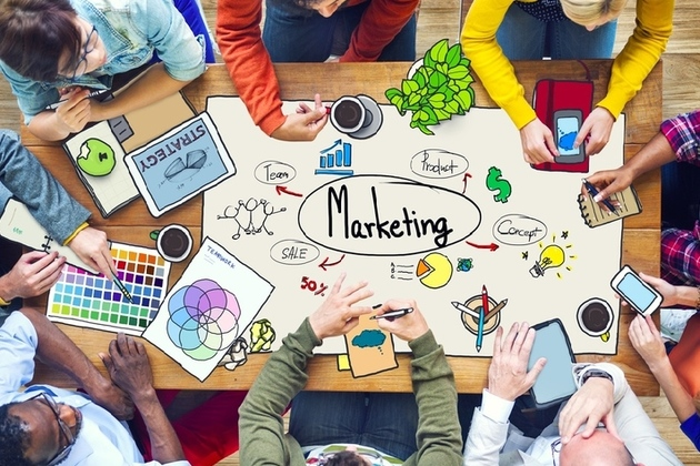 overhead image of group around table developing a marketing campaign