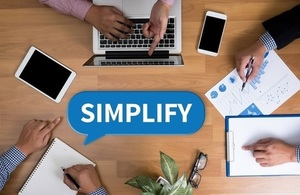 People sitting round desk with charts and laptops with the word simplify in a speech bubble in the middle
