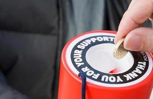 A person putting a coin in fundraising tin.
