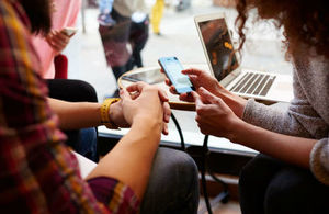 A woman and friend interact with a smart phone