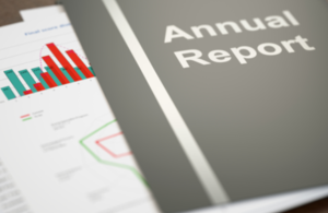 Copy of an annual report sitting on top of some papers containing charts