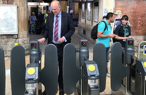 Picture of Chris Grayling using the ticket barriers.