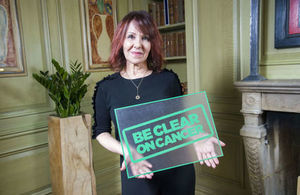 Arlene Philips holding a Be Clear on Cancer sign
