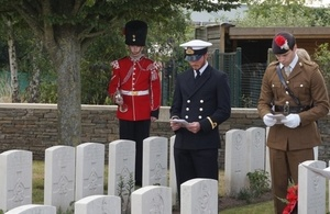 (l-r) Sub Lt Fred Warren-Smith, Military Attaché to the Defence Attaché The Hague and Lt Alexander Edmund from the Royal Regiment of Fusiliers pay their respects to 2 Lt Swallow as bugler LCpl Thomas Bewlay looks on. Crown Copyright, All rights reserved.