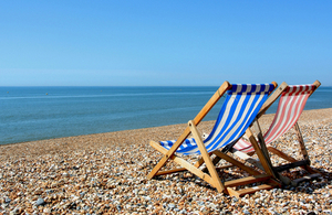 deckchairs facing out to sea on a pebble beach