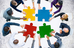 large jigsaw pieces being brought together by people on a round table