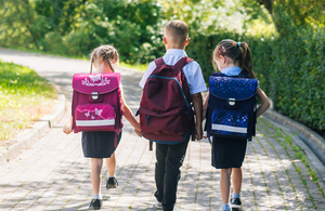 the backs of 3 school children walking to school with backpacks on