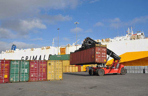 Image of shipping containers being moved in a port.