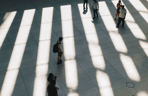 People standing in between strips of light and shadows on the ground.