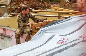A Royal Marine Commando engineer helps to fix a tarpaulin shelter kit supplied by UK aid to a house on the British Virgin Island of Tortola that was badly damaged by Hurricane Irma. Picture: MOD