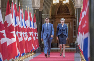 Canadian PM Justin Trudeau and UK PM Theresa May walking alongside Canadian and UK flags