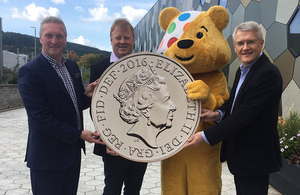 Jonathan Rigby, Children in Need, Adam Lawrence, Royal Mint and Andrew Jones, Exchequer Secretary to the Treasury with Pudsey and giant 'round pound' coin