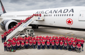 Invictus Games UK Team posing in front of an Air Canada plane at London Heathrow.