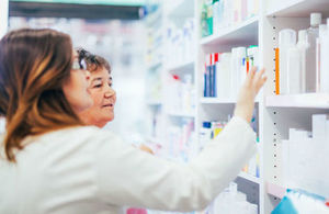 Pharmacist and customer search for medication on a pharmacy shelf