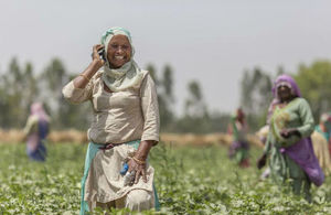Woman using a mobile phone in field of crops