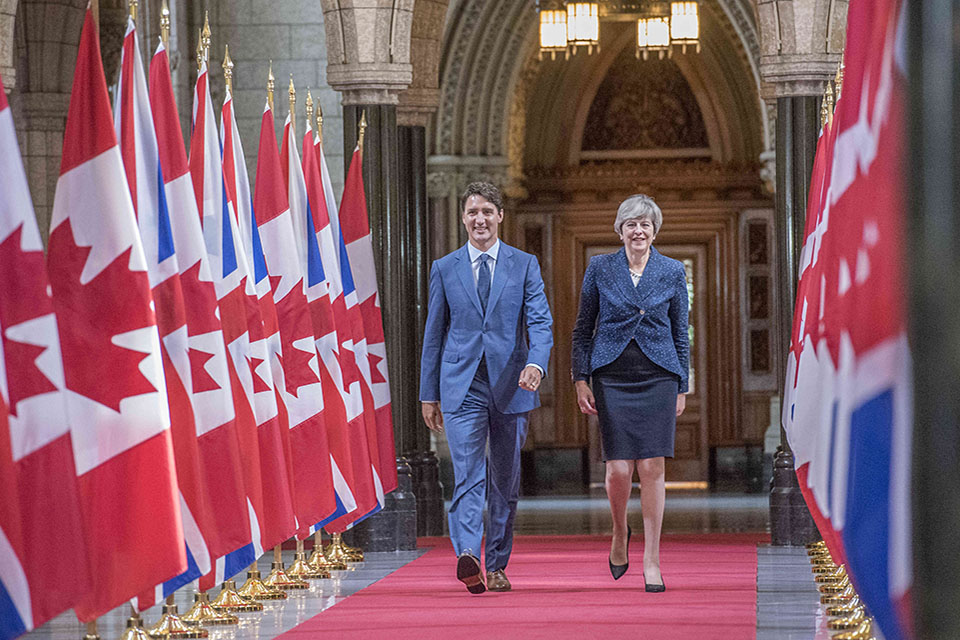 PM Theresa May and Canadian PM Justin Trudeau walking along UK/Canadian flags