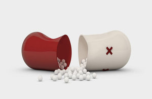 A red and white capsule split in half with small white balls coming out