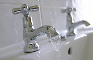 Two water taps with flowing water